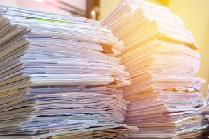 documents on desk stack up high