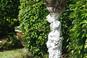 Statue of cupid in cozy garden