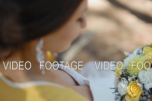Young woman hold yellow bouquet in her arms. Wedding photo session.