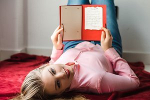 Young smiling blonde girl with long hair lying on bed and holding hand-made card in her hands