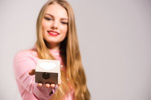 Portrait of a young smiling blonde girl giving small wooden box with heart