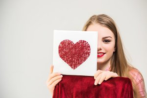 Portrait of young smiling pretty blonde long-haired girl holding hand-made artwork with heart in her hands