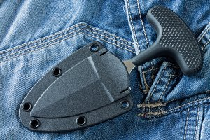 Urban knife in case on jeans background. Diagonal position.