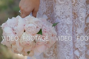 Bride hold wedding bouquet, groom touch her hand