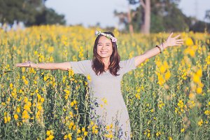 asian woman enjoying in yellow field