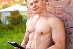 Young athlete outdoors, look, resting against the wall, holding a tablet, listening to music. A bright sunny day in nature, jeans fashion style, urban life.