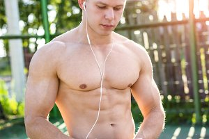 Athletic man with a clipboard watching a movie, listening to music in the summer in open air concept bodybuilder, vacation in city of headphones. Looks social networks.