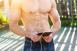 Athletic with a clipboard watching a movie, listening music in summer in open air concept bodybuilder, vacation in city of headphones. Looks social networks.