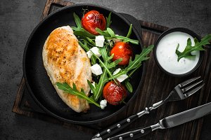 Grilled chiken fillet and fresh salad with white sauce.