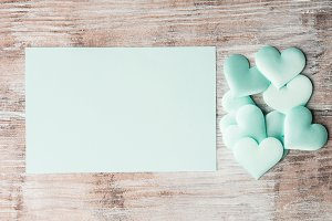 Green pastel hearts and paper invitation card