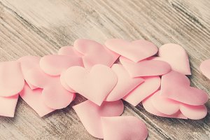 Pink hearts on textured wooden table. Toned banner