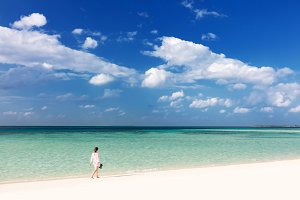 Woman walking on tropical beach in Maldives