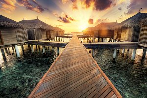 Wooden jetty and water villas. Maldives island resort at sunset