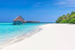 Panorama of wide sandy beach on a tropical island in Maldives, Indian Ocean.