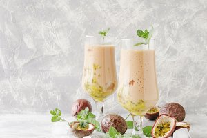 pink milkshake with ice cubes and mint leaves and fruits of passion fruit on a marble table, selective focus