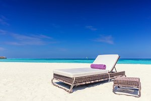 Deckchair on sandy tropical beacha a small island resort in Maldives, Indian Ocean