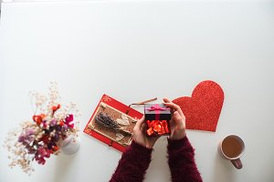 Female hands opening a gift with flowers and heart on table