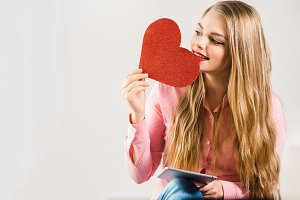 Portrait of a young smiling blonde girl with long hair holding tablet and heart in hands on white background