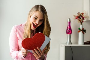 Portrait of a young smiling blonde girl with long hair holding tablet and heart in hands