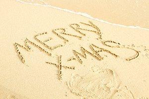 Merry xmas written on sand