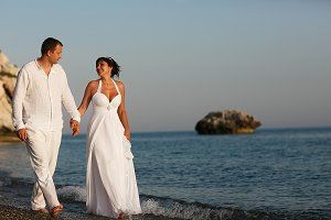 Tanned wedding couple walks