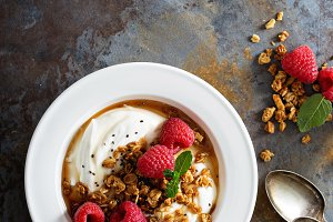Yogurt bowl with raspberry and maple syrup