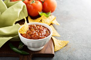 Red tomato spicy salsa with chips