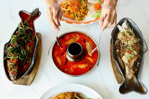 Top view of Thai Asian cuisine chef preparing Tom yum goong and seafood dishes