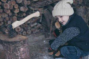 little boy chopping firewood
