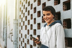 child with the mobile phone listening to music on the street