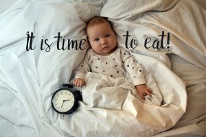 Child with an alarm clock lying on the bed, and wishes everyone a good morning. time to work. Time to sleep. Top viev