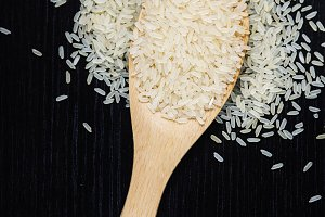 Golden uncooked rice on wooden spoon