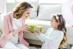 Girl presenting gift to happy mother