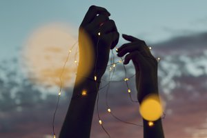 Silhouette of hands holding lights
