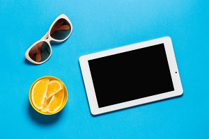 Creative Workspace Table With White Tablet and Sunglasses Bright Oranges on Blue Copy Space
