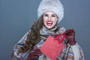 Portrait of smiling elegant woman holding small red shopping bag