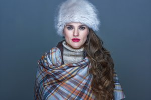 Portrait of young elegant woman in fur hat isolated on cold blue