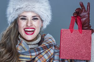 Portrait of smiling elegant woman showing small red shopping bag