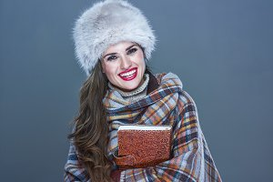 smiling modern woman in fur hat isolated on cold blue embracing book