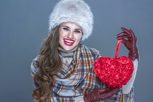 happy modern woman isolated on cold blue holding red heart