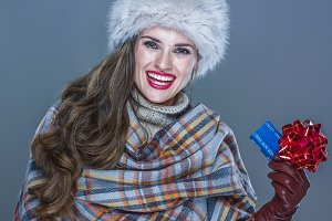 Portrait of smiling woman with credit card with red ribbon