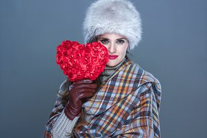 trendy woman isolated on cold blue background with red heart