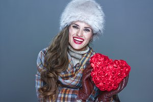 happy woman isolated on cold blue background showing red heart