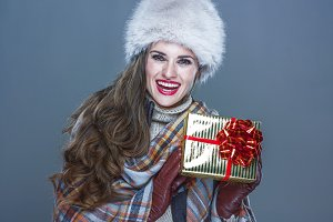 happy young woman isolated on cold blue showing present box