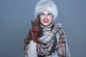 smiling elegant woman in fur hat isolated on cold blue got idea