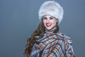 Portrait of happy elegant woman in fur hat isolated on cold blue