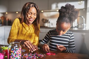 Attractive parent helping child with bead project