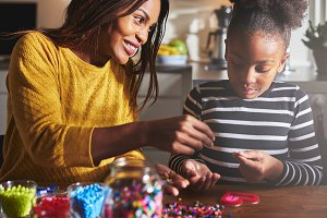 Smiling parent helping child with craft project