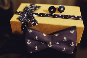 Violet bow tie lie behind a box