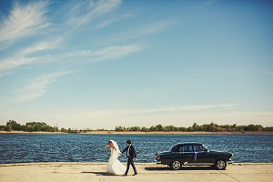 Newlyweds walk out of an old car